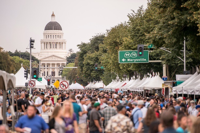 an image of last years Brewfest with hundreds of people on the Capitol Mall in Sacramento with the Capital building in the background